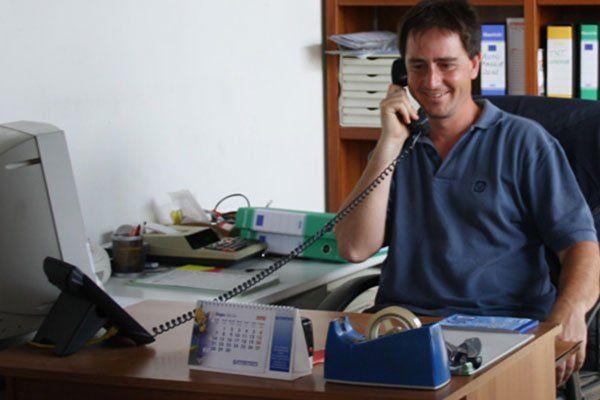 un uomo seduto alla scrivania mentre parla al telefono