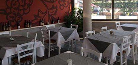 Tavoli con tovaglie di color grigio e bianco all'interno di un ristorante