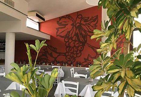 Vista dall'alto dei tavoli con tovaglie di color grigio e mensola lunga con bottiglie di vino all'interno di un ristorante