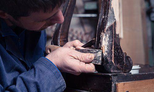 operaio mentre effettua un lavoro di restauro - Larizza restauro mobili a Torino