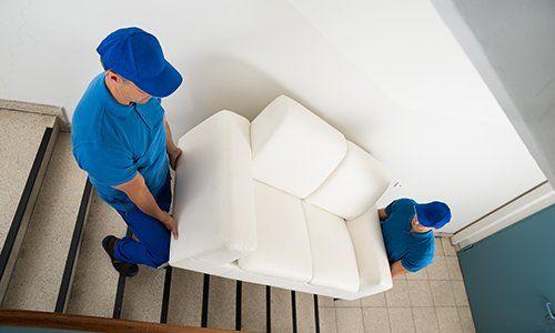 operai mentre trasportano un divano - Larizza Restauro Mobili a Torino