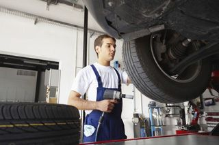 Mechanic installing auto tires in London, KY