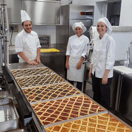 tre pasticceri sorridente di fronte a cinque taglie di crostata