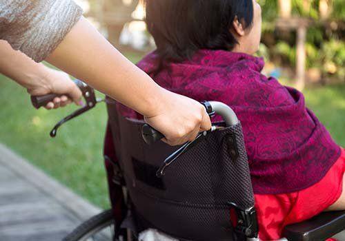 Mani amiche spingendo una sedia a rotelle