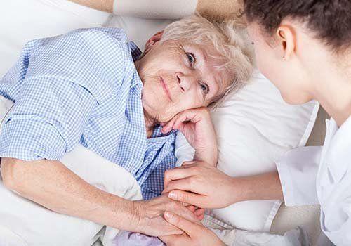 vecchia al letto servita da un'infermiera