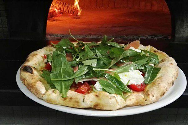 una pizza vicino a un forno a legna
