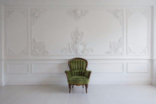 salone con parete con stucchi in rilievo e una poltrona verde centrale
