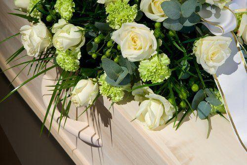 composizione floreale su una bara in legno chiaro