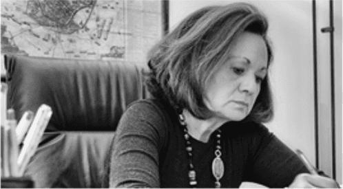 una donna seduta su una poltrona d'ufficio che scrive su un foglio