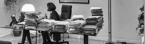 una donna seduta alla scrivania con una pila dii documenti