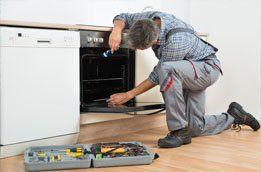 man repairing an oven
