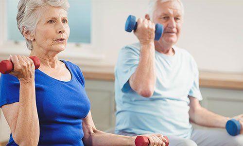 delle persone anziane che fanno esercizi con dei pesi