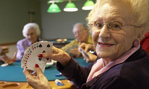 una signora anziana sorridente con delle carte in mano