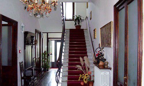 l'interno di una casa con un lampadario, vasi di fiori e una scala con una moquette bordeaux