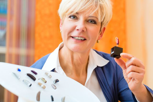 woman holding hearing aids