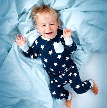 bambino biondo gioca sul letto
