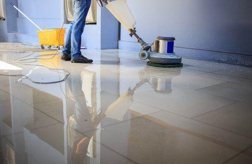 operaio mentre pulisce pavimento con una macchina di pulizia