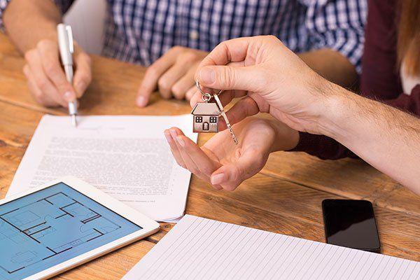 Una persona che firma un contratto di casa mentre riceve un mazzo di chiavi