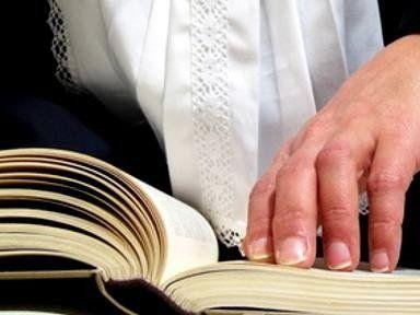 la mano di un uomo cche indossa un bavero bianco mentre sfoglia un testo di legge