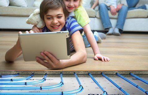bambini che guardano un tablet su un pavimento riscaldato