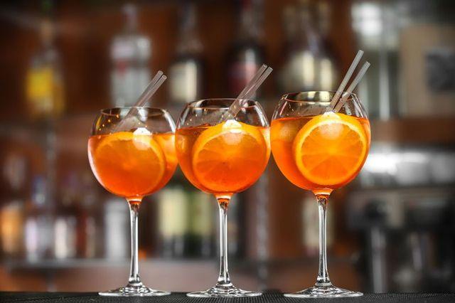tre calici con dei cocktail con fetta di arancia e cannucce - Genova