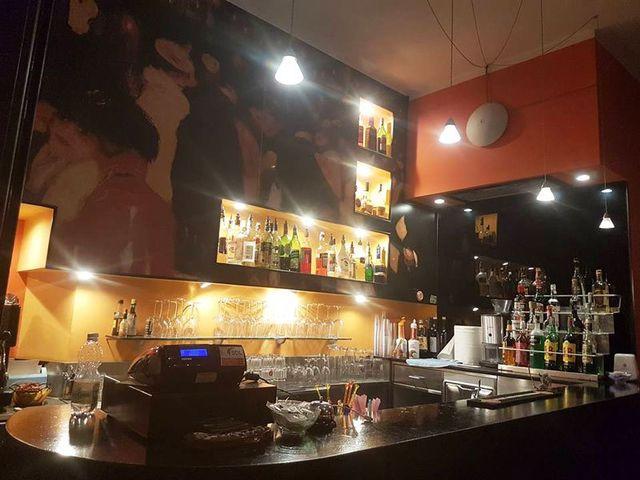 vista del bancone di un bar con cassa, liquori muri arancioni e color sabbia - Genova