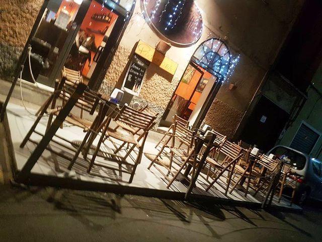 bar visto da fuori con sedie in legno, tavolini rotondi due porte d'entrata in vetro e decorazioni con luci blu