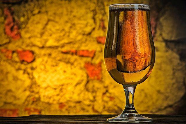 un cocktail di color rosa in un bicchiere con una cannuccia