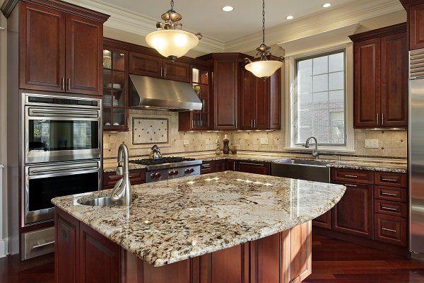 una cucina con mobili in legno e penisola con top in marmo