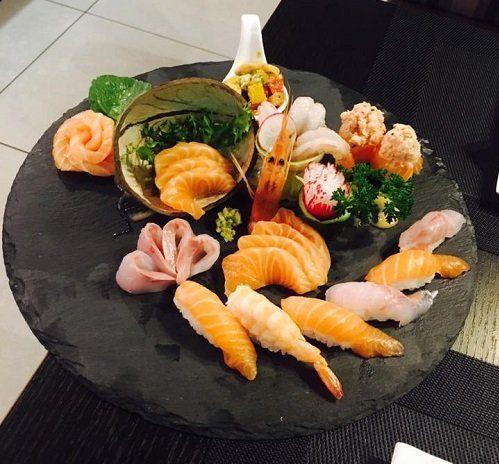 un tagliere di sushi misto con salmone, tonno e gamberi