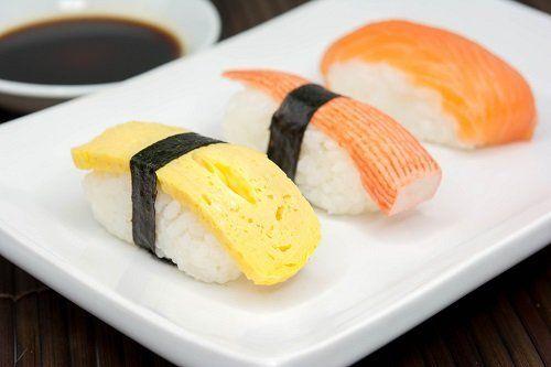 un piatto di sushi con formaggio, surimi e salmone