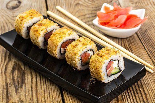 un vassoio di sushi al tonno e accanto una ciotola con dello zenzero fresco