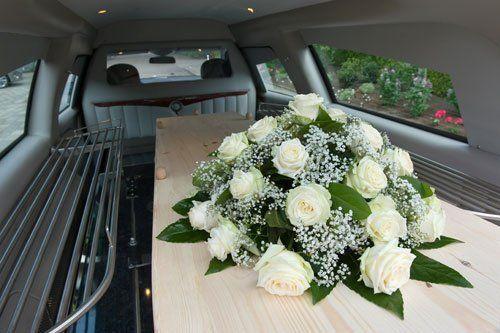 carro funebre con bara e fiori bianchi