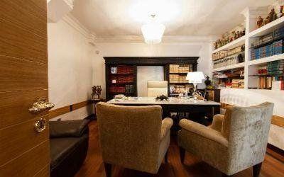 un ufficio con due poltrone una scrivania e delle librerie