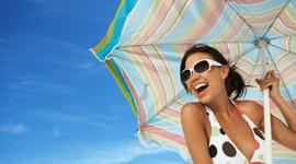 donna al mare con ombrellone ed occhiali da sole su sfondo cielo blu