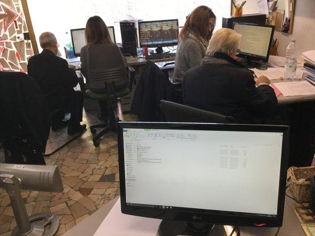 Impiegati al lavoro da Berus con monitor in primo piano