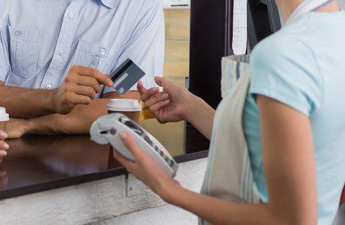 cassiera prende una carta di credito per il pagamento