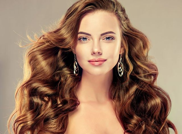 Una donna con occhi azzurri e capelli castani mossi e lunghi