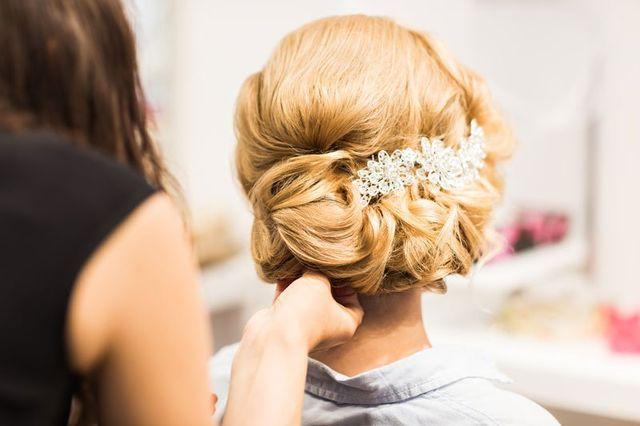 Una parrucchiera sta sistemando i capelli a una donna vista di spalle con capelli raccolti biondi con una molletta a forma di fiore