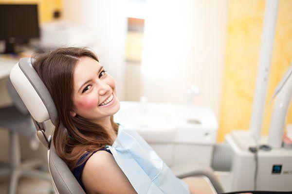 una donna seduta sorridente su una sedia da dentista pronta per la visita