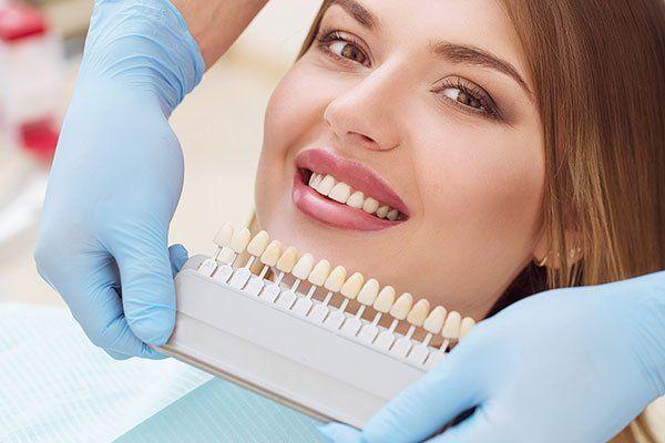 una donna sorridente e due mani di un dentista che mostrano dei denti artificiali