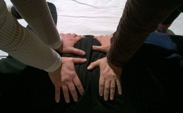 due persone premono la mani sulla schiena di una persona seduta