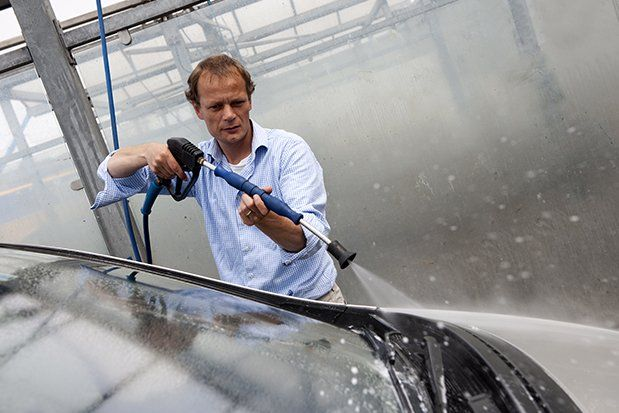 Man washing the windscreen of his car in a cubicle