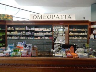 vista frontale di uno scaffale assortito di prodotti con su scritto OMEOPATIA