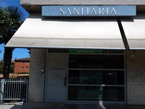 vista esterna di una farmacia con insegna SANITARIA