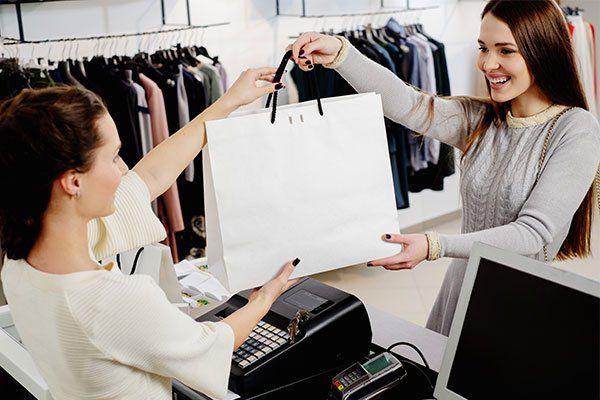 cliente donna sorridente alla cassa riceve busta bianca con acquisti moda