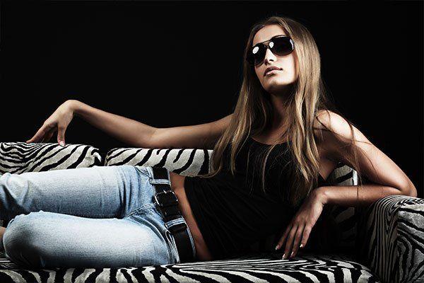 modella in occhiali da sole e jeans e canotta nera posa su divano zebrato