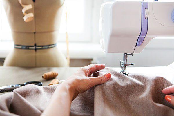 mani femminili fanno riparazione sartoriale con macchina da cucire