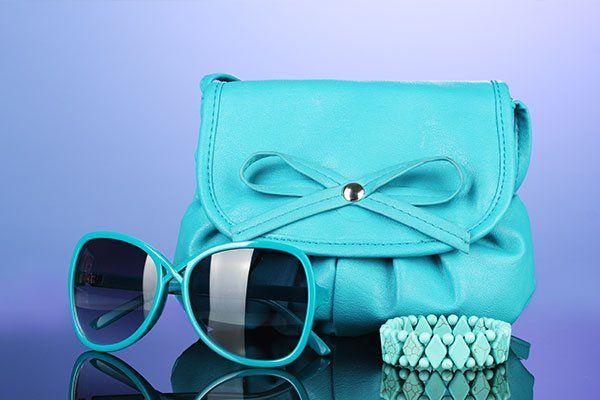 occhiali da sole, un bracciale e una borsa clutch celesti
