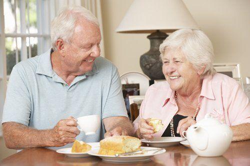 Una coppia di anziani che beve tè e mangia dolcetti